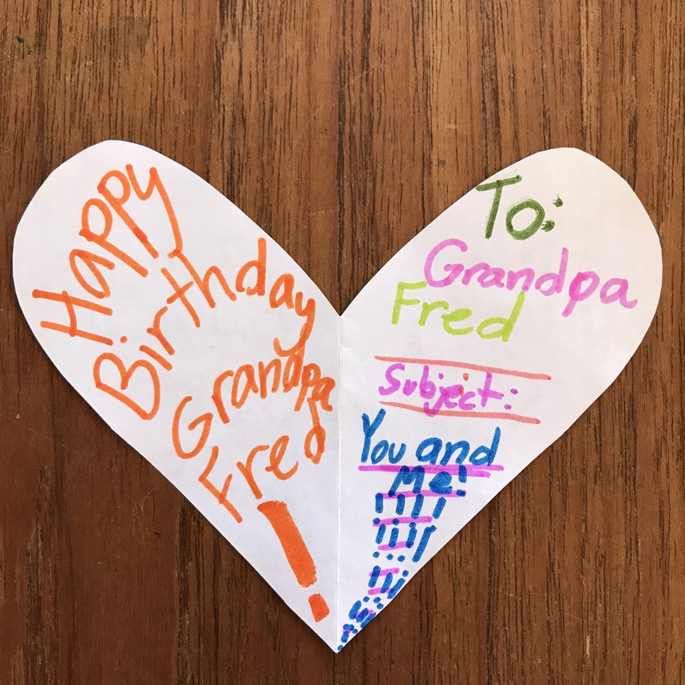 A heart-shaped card cut from printer paper is decorated as a birthday card for a deceased great-grandfather